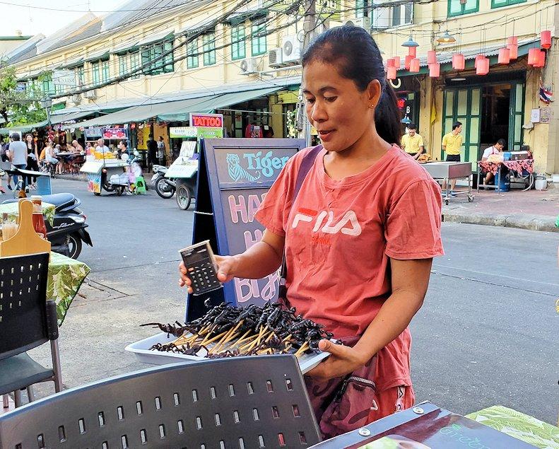 バンコク市内のカオサン通りでサソリを売るオバサン
