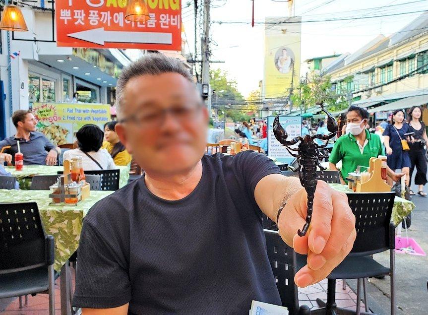 バンコク市内のカオサン通りでサソリを売るオバサンからサソリを買う