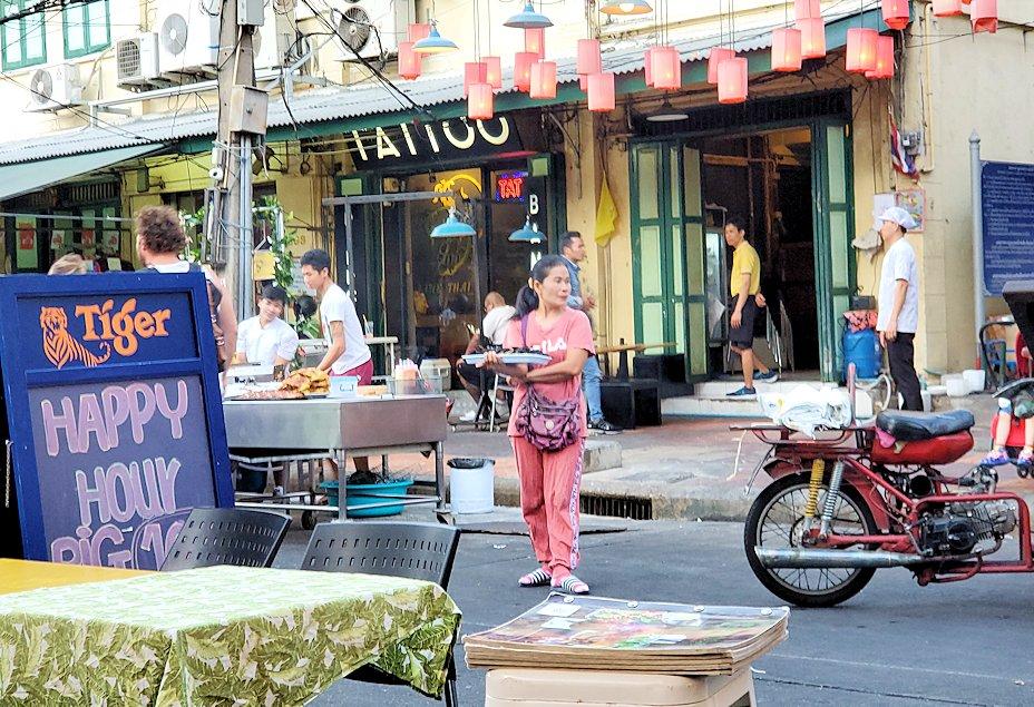 夕暮れ時のカオサン通りでまだサソリを売るオバサンの姿