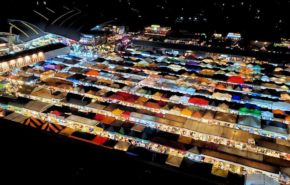 バンコク市内のラチャダー鉄道市場の夜景を、建物の駐車場から見下ろす