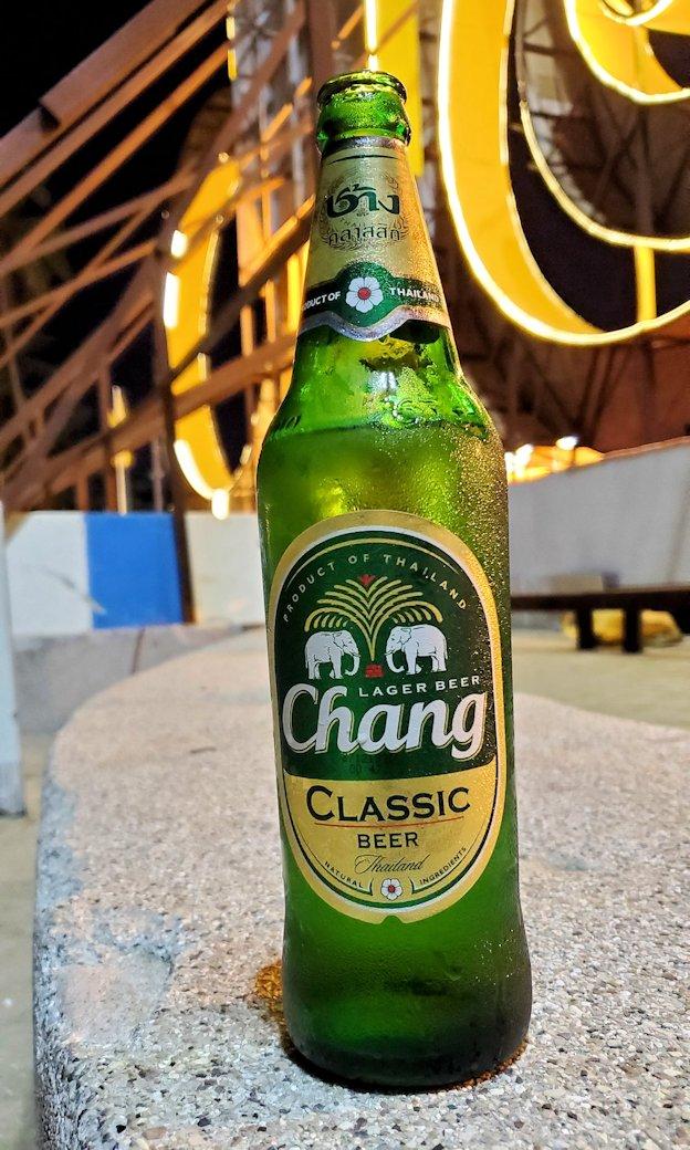 夕暮れ時のパタヤのビーチ沿いでチャンギビールを味わう