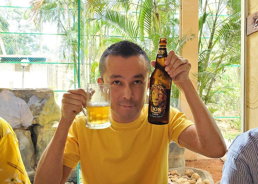 アヌラーダプラにある「ヘリテージ ホテル」のレストランでスリランカカレーとビールを味わう男