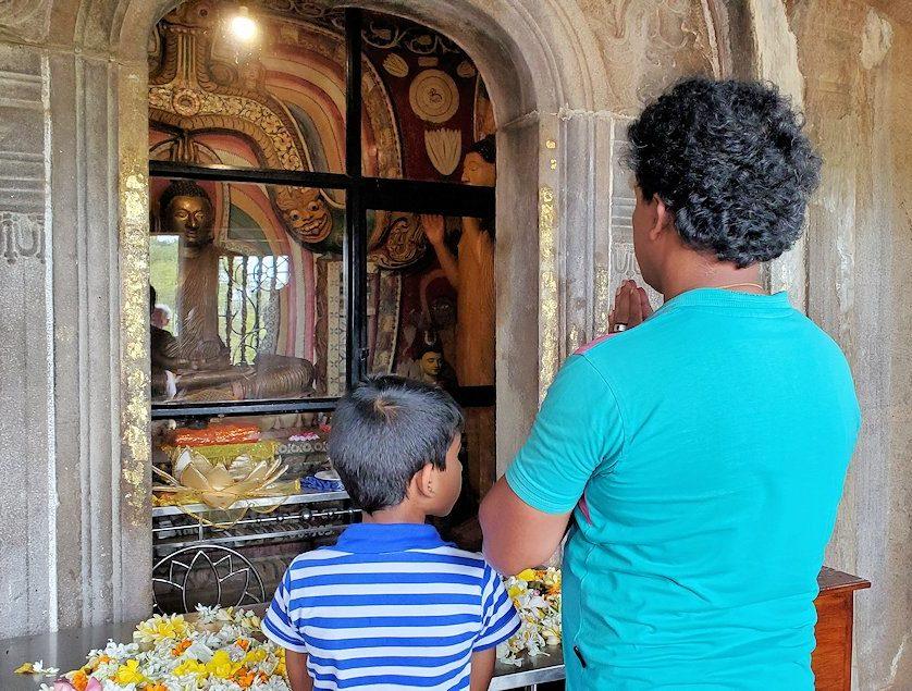 アヌラーダプラのイスルムニヤ精舎の本堂で祈る、現地の親子