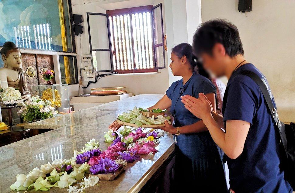 祀られているスリー・マハー菩提樹を祀る仏堂にある仏像に祈る人達-2
