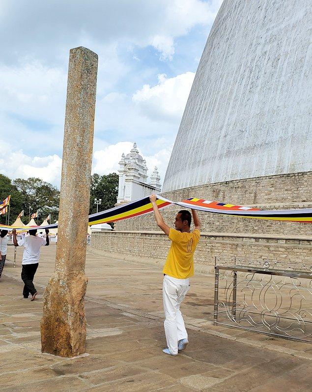 ルワンウェリ・サーヤ大塔周囲で仏旗を担いで歩く男-3