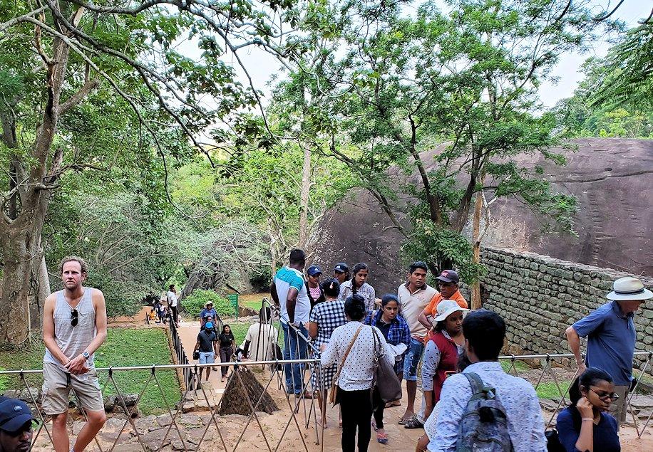 シギリヤロック手前から階段を登って行く所にある、大きな門のような巨岩の間を進む人達