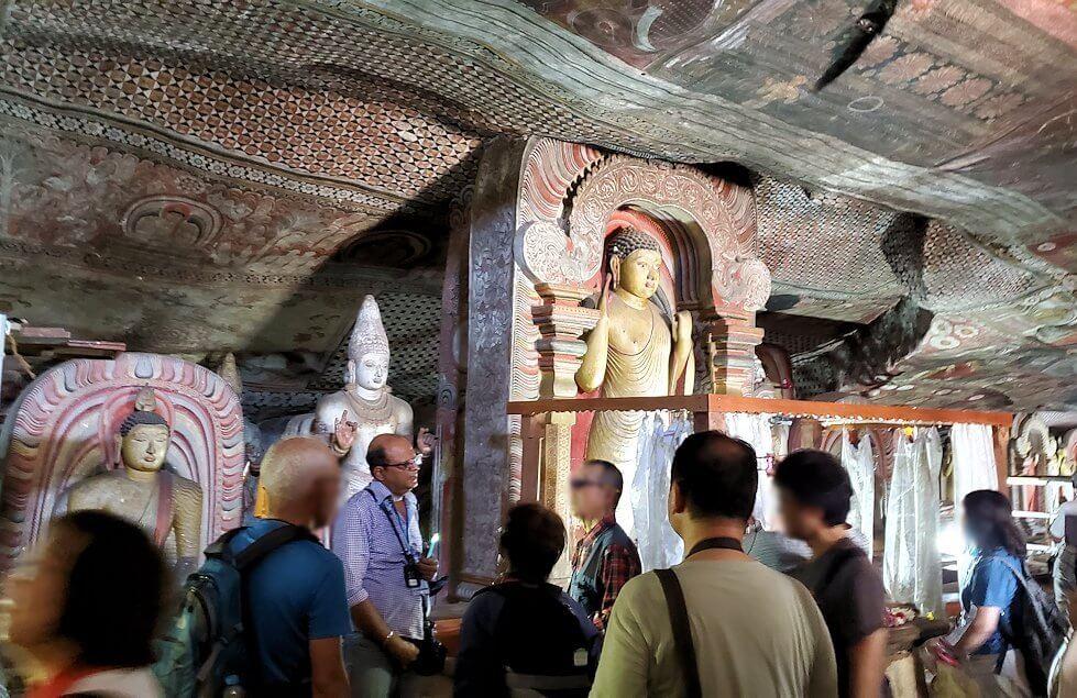 ダンブッラの石窟寺院内の第二洞窟に設置されている仏像の数々を眺める人達