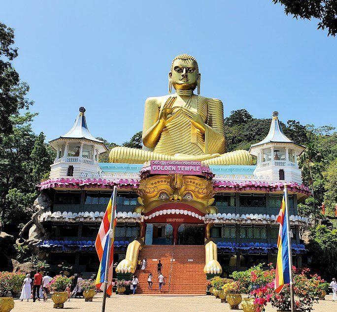 ダンブッラ寺院の見学を終えて、坂を降りて行く途中に見えてきた黄金の仏像がある建物をバックに記念撮影-3