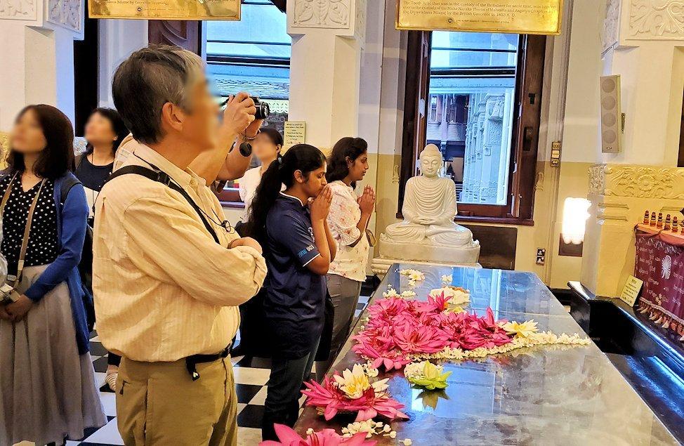 キャンディの仏歯寺の礼拝堂に飾られている沢山の仏像に祈る人達