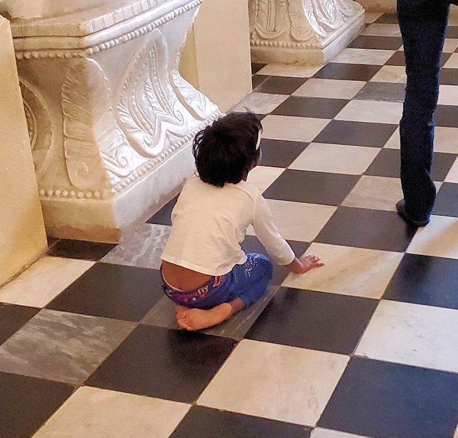 キャンディの仏歯寺の礼拝堂で膝まづいていた子供