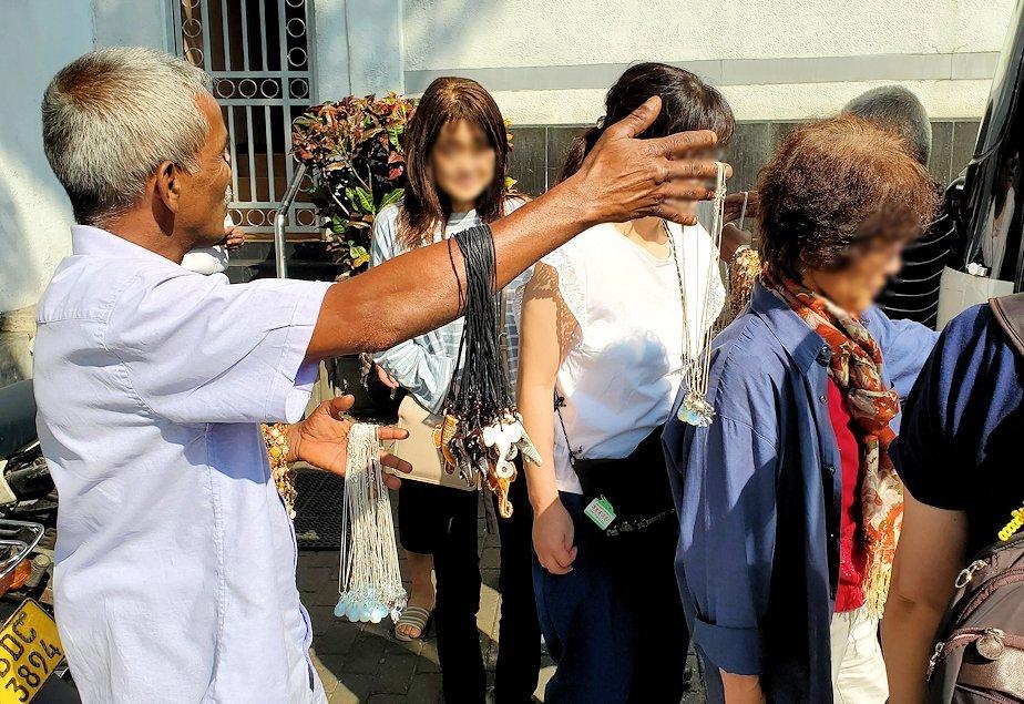 キャンディ近くの宝石専門店前で安いアクセサリーを売るオジサン