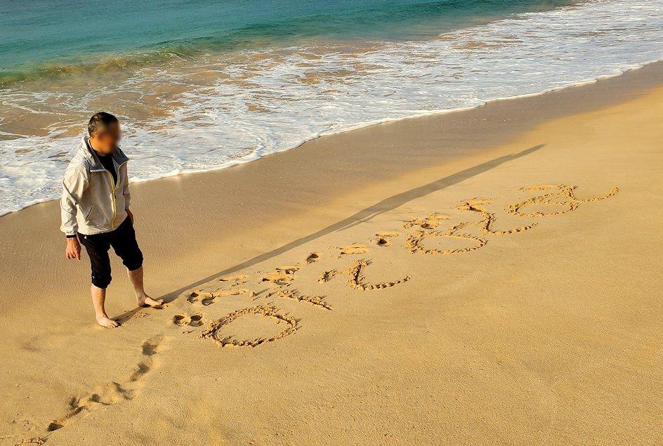 「ロング・ビーチ・リゾートホテル」のビーチで砂浜の文字を眺めるオジサン