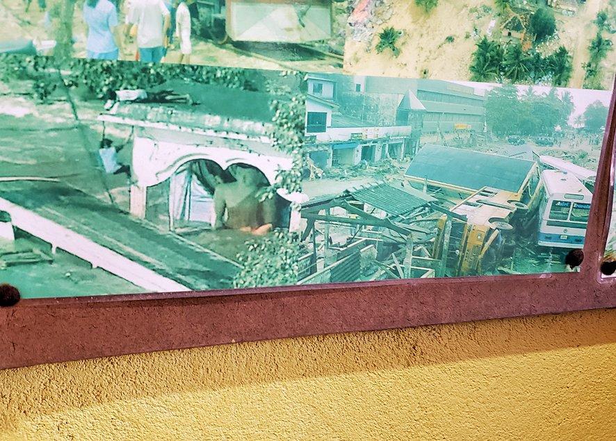 「津波本願寺仏舎」の記念館内に飾られた、被害当時の写真を見る人達-4