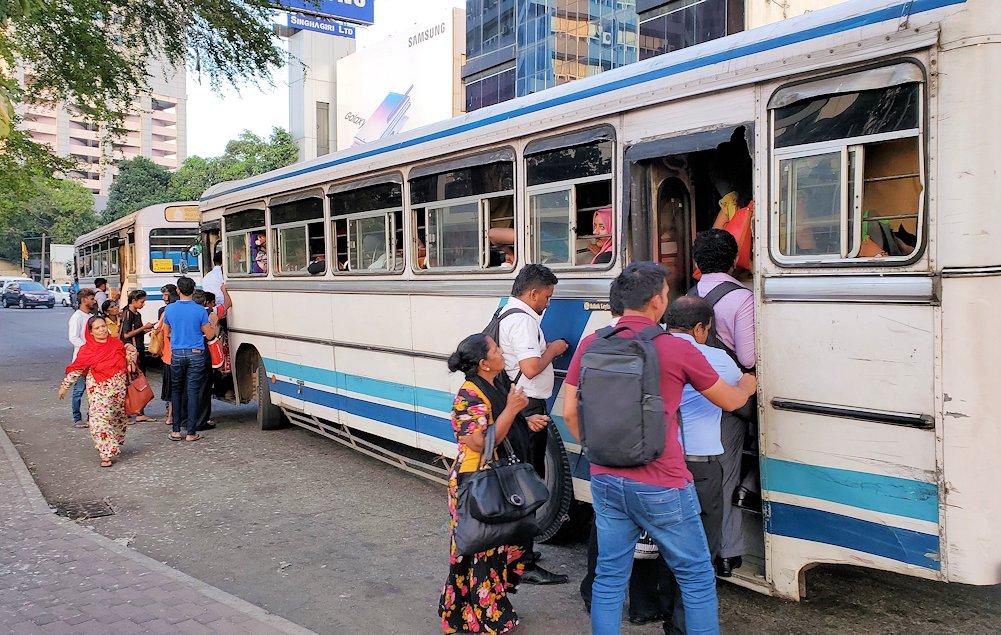 コロンボ市内を走る、窓が全開のボロいバスに乗り込む人達