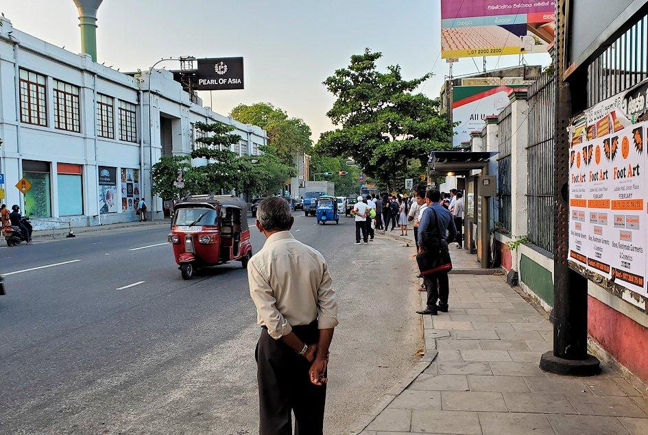 コロンボ市内の道路脇でバスを待つ人達