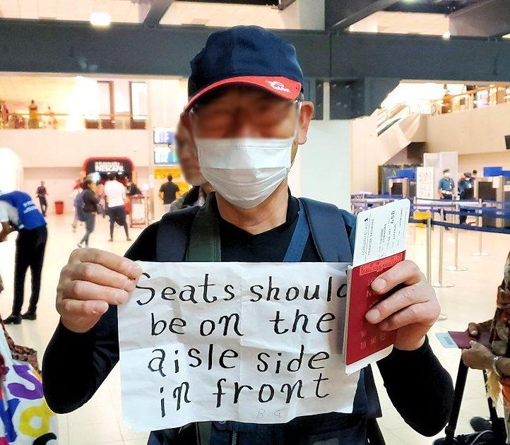 バンダラナイケ国際空港のチェックインカウンターで見せる紙を持つオジサン