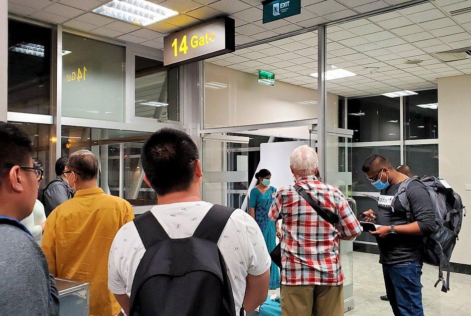 スリランカの空港に待機しているシンガポール航空の飛行機に乗り込む人達