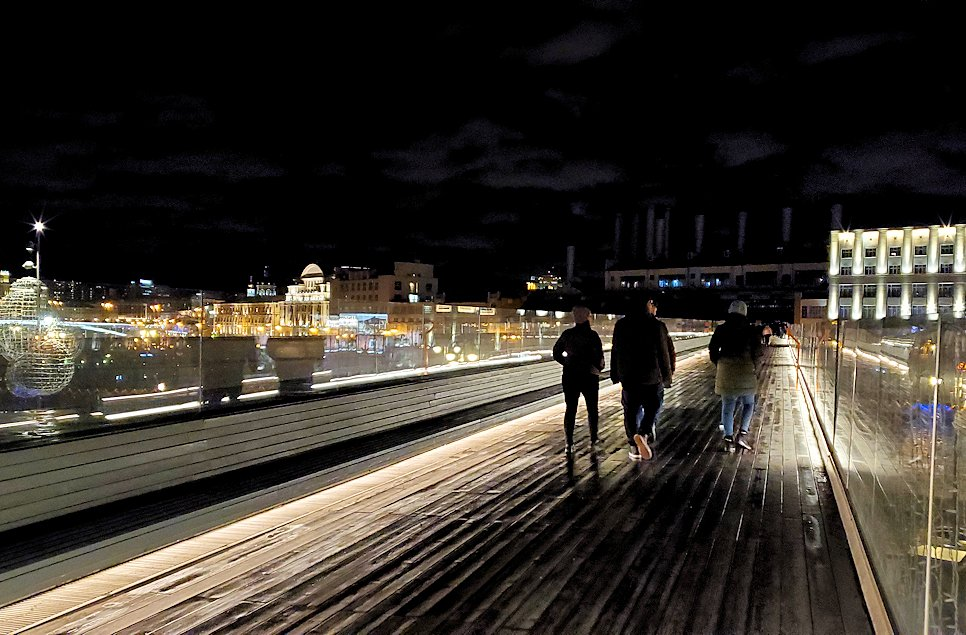 夜のモスクワ川沿いにあるパリシャー橋を歩く人