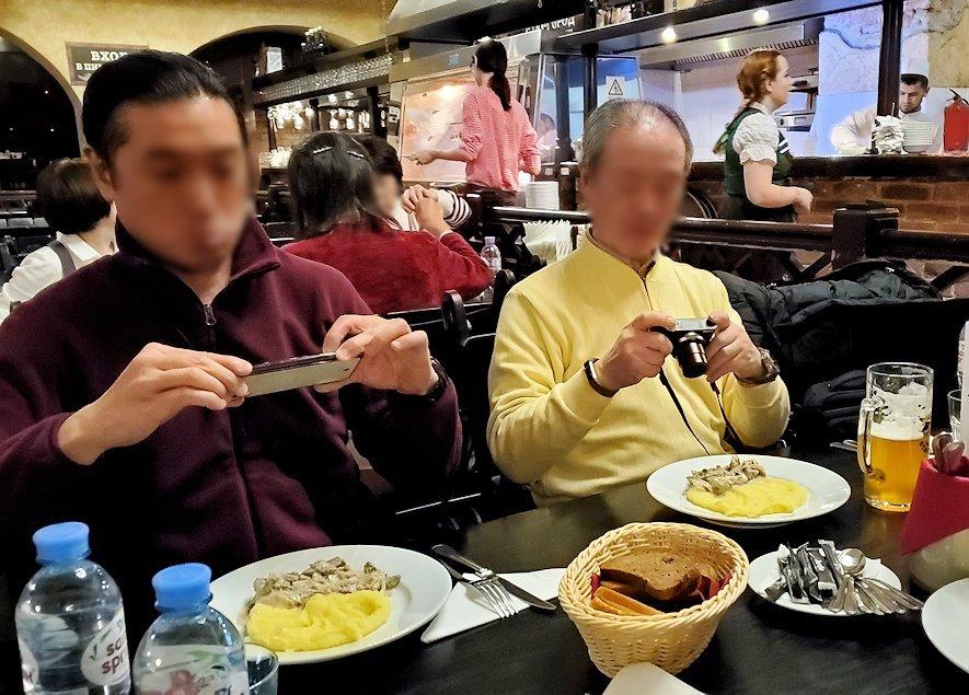 マッシュポテトが添えられたお肉を写真に撮る人達