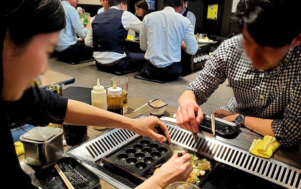 大阪梅田のたこ焼き屋で自分達で焼いて食べるお店を訪れる